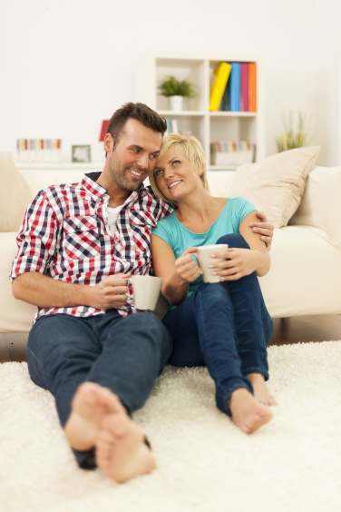 cool couple sitting under new split system air conditioning unit