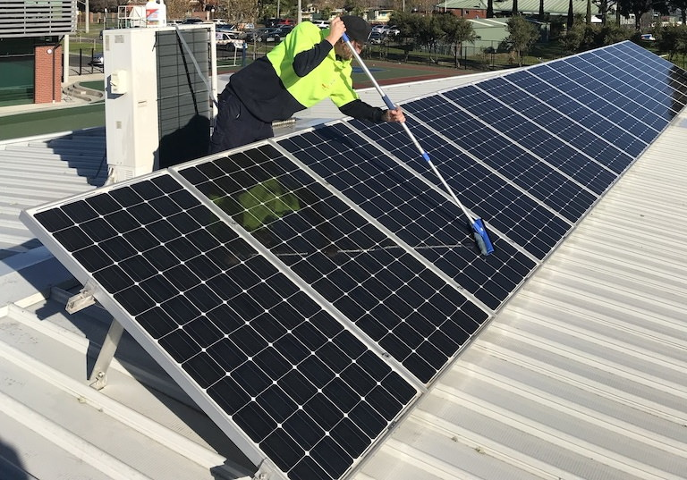 electrician cleaning solar panel